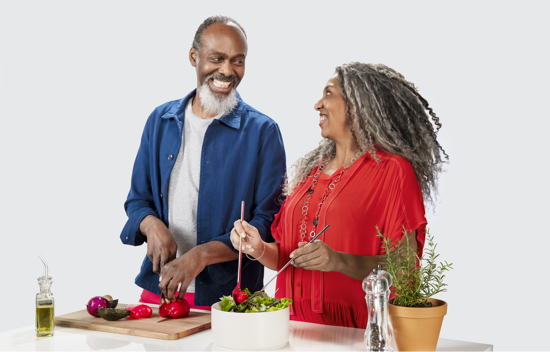 Happy couple cooking a healthy meal together to lower their cardiovascular risk